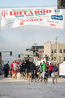 Hugh Neff and team leave the ceremonial start line with an Iditarider at 4th Avenue and D street in downtown Anchorage, Alaska during the 2015 Iditarod race. Photo by Jim Kohl/IditarodPhotos.com