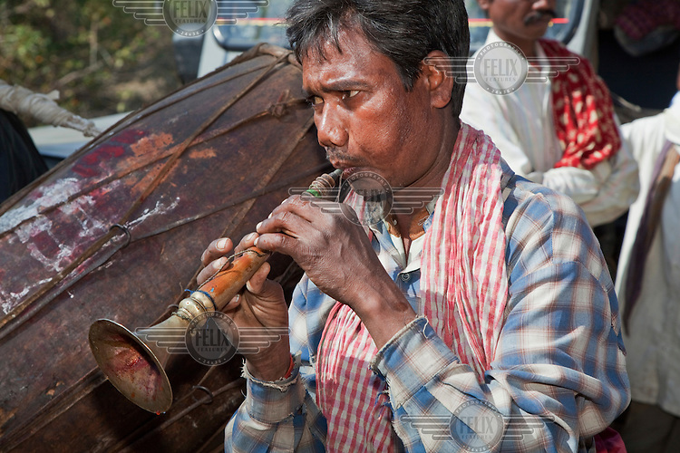 A Santhal Adivasi musician plays at a wedding while guests await the arrival of the groom at the beginning of a daylong wedding party in the village of Jorakath.