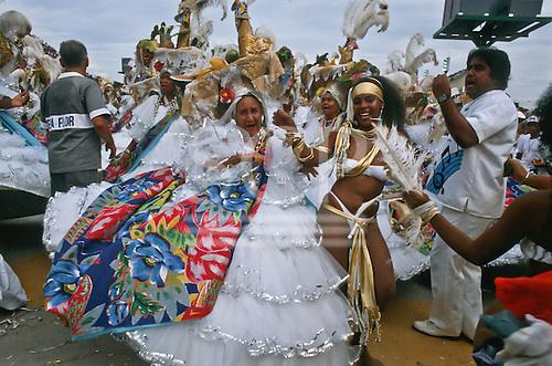 Rio de Janeiro, Brazil. Samba dancers during the carnival parade; older women in full dress, younger woman in bikini.