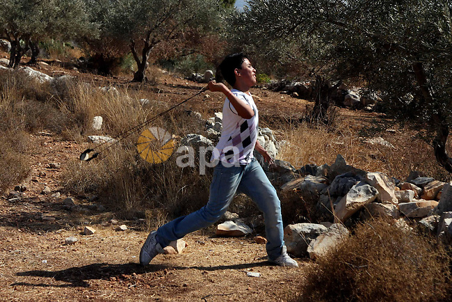 Palestinian protestor uses a slingshot to hurl stones toward Israeli soldiers during a demonstration against Israel's separation barrier in the West Bank village of Bilin, near Ramallah on Sep 25, 2009. Photo by Issam Rimawi