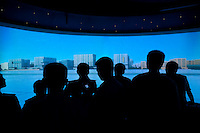 Silhouettes of people viewing a projection in the Shanghai Urban Planning Exhibition Center in Shanghai.  © LAN