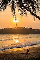 Mirissa, tourist sitting on Mirissa Beach watching the sun set, South Coast of Sri Lanka, Southern Province, Asia. This is a photo of a tourist sitting on Mirissa Beach watching the sun set, Sri Lanka, Asia. Mirissa Beach, a palm tree lined beach on the South Coast of Sri Lanka is one of the most popular tourist beaches and is host to many a beautiful sun set.