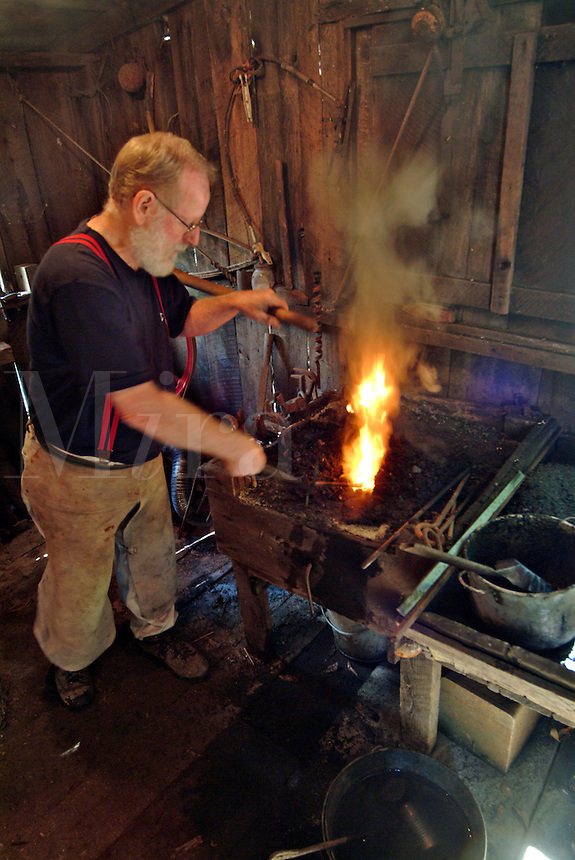 A blacksmith prepares the coal fed fire before working on a metal tool at a saw mill in Occidental California.