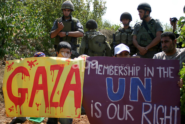 Israeli soldiers stand guard as Palestinians demonstrate along with left-wing Israelis and foreign peace activists in Beit Omar, near the West Bank city of Hebron on August 20, 2011 for the creation of a Palesitnian state and gainst the latest Israeli air strikes on Gaza in which 14 people were killed and around 40 wounded, according to Palestinian sources.Photo by Najeh Hashlamoun.