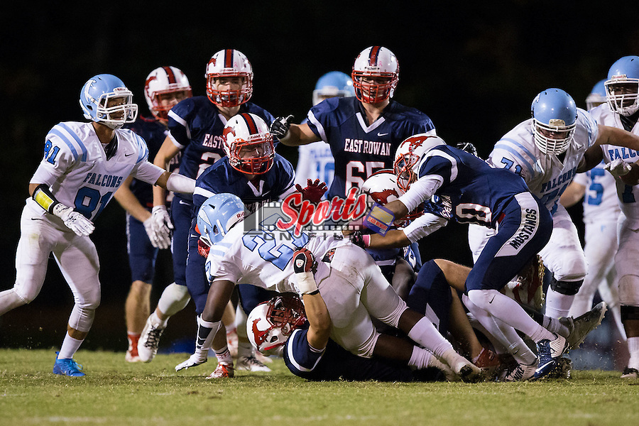 Martavio Rankin (27) of the West Rowan Falcons is tackled by a host of East Rowan Mustangs defenders during first half action at East Rowan High School on October 15, 2015, in Salisbury, North Carolina.  The Falcons defeated the Mustangs 28-7.  (Brian Westerholt/Sports On Film)
