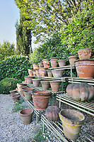 A number of terracotta pots are arranged on a metal shelving unit in the corner of a garden.