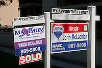 """For sale"" signs for Maximum realty and Re/Max are seen next to each other in Winnipeg Thursday May 26, 2011."