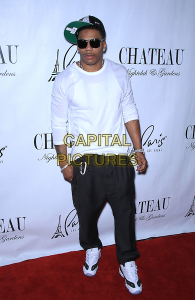 Nelly (Cornell Iral Haynes, Jr.).at Chateau Nightclub and Gardens inside Paris Las Vegas, NV, USA, .2nd September 2011..full length top baggy trousers trainers green cap hat smiling black sunglasses white  earrings diamonds moustache mustache facial hair .CAP/ADM/MJT.© MJT/AdMedia/Capital Pictures.
