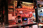 Meat stall butcher selling Jamon Iberico joints, Mercado San Miguel market, Madrid city centre, Spain