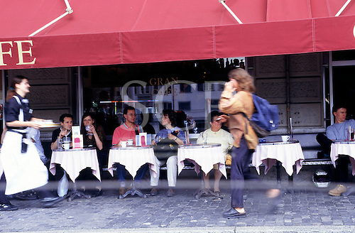 Zurich, Switzerland. Blurred picture of a girl walking front of a cafe; waitress and guests.