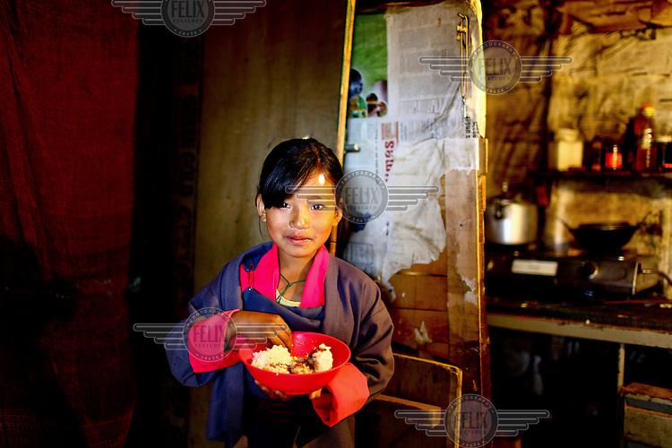 A girl eats inside her hut in the kala bazaar slum.