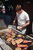 Man cooking meat on outdoor barbecue,