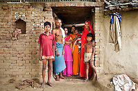 "(L-R) Amit (13), Tribhuvan Adivasi (50), Dharma (18, soon to be married), Vinita (23, married when 14, has 3 children), Vinita's baby, Kelaji Adivasi (45), and Akanksha (8) stand in the doorway of their house. Tribhuvan, a farm labourer, says that ""it was a mistake to have so many children. Food is difficult for us."" Kelaji and Tribhuvan have a total of 6 children and live in poverty in Baul ka Dhera hamlet, Mugari Village, Allahabad, Uttar Pradesh, India. Allahabad, a poorer district of the state of Uttar Pradesh, is the most populated district of the most populous state of India. While Ghaziabad, located close to India's capital city, Delhi, has a population of 4,661,452 with a sex ratio of 878 girls against every 1000 boys, and a high literary percentage of 85%, Allahabad, has a population of 5,959,798 and a sex ratio of 902 girls against every 1000 boys and a literacy rate of 74.41%. Photo by Suzanne Lee / Panos London"