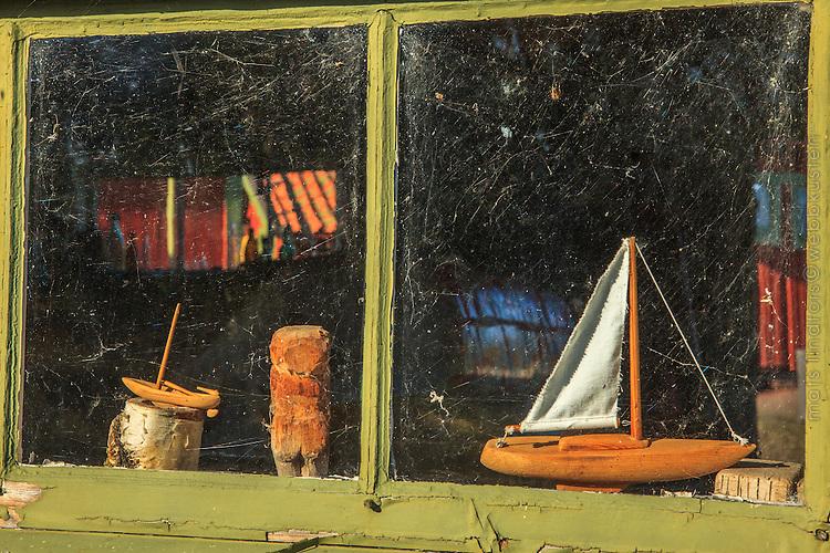 Prydnadsbåt i fönster på sjöbod på Långviksskär i ytterskärgården i Stockholm.