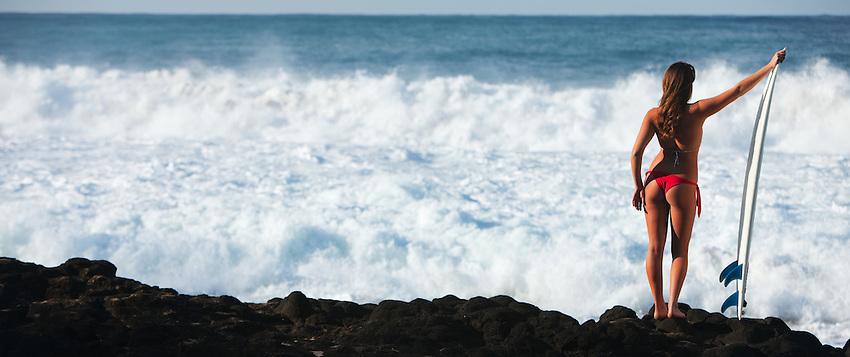 Hawaiian landscape with beautiful female surfer in bikini posing on lava rocks.