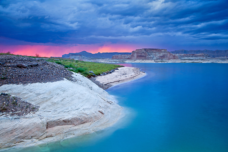 Viewed from the Lone Rock area of Lake Powell in Arizona, the sunset highlights a distant monsoon squall passing over the cliffs of the Grand Staircase-Escalante National Monument in Utah.