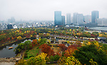 Osaka Castle Park and Chuo-ku financial distric city skyline aerial view with tourist boats and Gokurakubashi bridge on a misty autumn morning. Chūō-ku ward, Osaka, Japan 2017