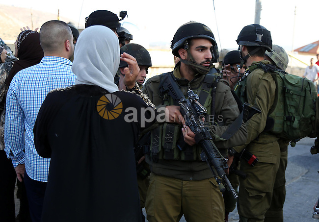 Palestinians argue with Israeli soldiers in the village of Kafr Malik, northeast of Ramallah on June 14, 2015, after clashes that resulted in the death of 21-year-old Palestinian Abdallah Ghanayem. An army spokesman said that the Palestinian had died after he threw an incendiary device at a jeep and the vehicle overturned on him. Palestinian security sources said, Israeli soldiers killed Ghanayem by hitting him with their jeep during clashes near Ramallah in the occupied West Bank. Photo by Shadi Hatem