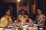David, his brother and brother-in-law, take their Orthodox Christmas morning meal. in Roma tradition, the women serve the men and sit on a separate table. The family is mixed Muslim and Orthodox, so both chicken as well as the traditional Christmas pig is served. Belgrade, Serbia January 7th 2005