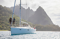 A couple stand on the bow of an anchored sailboat on the Na Pali Coast of Kaua'i.