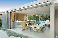 View from outside into a mid-century modern dining room and kitchen with movable aluminum walls