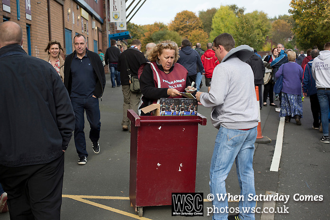 Burnley 1 West Ham United 3, 18/10/2014. Turf Moor, Premier League. A programme seller outside The fixture was won by the visitors by three goals to one watched by 18,936 spectators. The defeat meant that Burnley still had not won a league match since being promoted from the Championship the previous season. Photo by Colin McPherson.