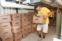 Alex Rajovic,'20, ducks as he moves boxes of magazines and books to a storage area in the basement of the Redwood Library in Newport as he and other freshmen take part in Salve's Exploration Day of Service.