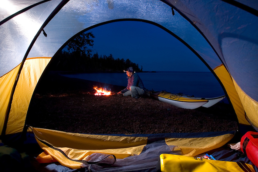 A sea kayaker tends a campfire as seen through a tent opening while camping at Fish Cove on the Keweenaw Peninsula near Copper Harbor Michigan.