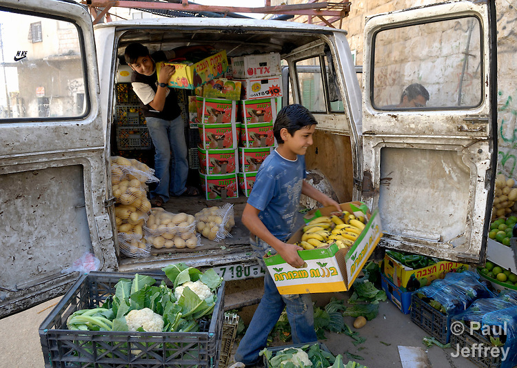 Boys unload produce for a shop in the Palestinian village of Shuqba, in the West Bank.