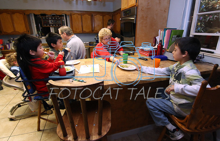 Roberta Simon passes Joey, 8, his dinner at their Mound House, Nev. home, on Monday, Dec. 19, 2011. The family includes 21 adopted special-needs children..Photo by Cathleen Allison