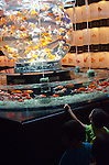 """September 8th, 2011: Tokyo, Japan - Kids look at a designer fish tank in the """"Art Aquarium"""" exhibition held at Nihonbashi Mitsui Hall in Tokyo, Japan. There are over 1,000 of golden fish on display with colorful lights and uniquely shaped of tanks. Traditionally the goldfish is a common Japanese pet but they are rarely seen in such luxurious surroundings. The exhibition runs until Sunday 12th September and is open at night too as a bar."""