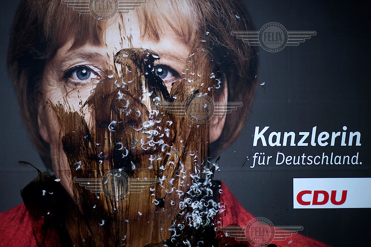 A 2013 election campaign poster of Angela Merkel with the slogan 'The Chancellor for Germany' (Die Kanzlerin fuer Deutschland). It has been covered with tar and feathers by her opponents.