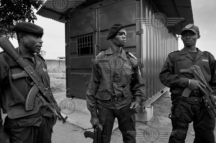A group of policemen stand outside a specially adapted shipping container used to securely store weapons. The containers were developed by MAG (Mines Advisory Group) with the explicit function of reducing the leaching of small arms and light weapons from state controlled armouries onto the black market.