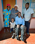 Sunny Nyamandwe (center) poses with his family at his home in Ruwa, Zimbabwe. Nyamandwe works at the National Rehabilitation Centre in Ruwa, which assembles and fits wheelchairs provided by the Jairos Jiri Association with support from CBM-US. Nyamandwe is one of the beneficiaries of the program. His legs remain paralyzed after an automobile accident more than two decades ago.
