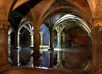 "General view of Manueline Cistern of the El Jadida (Mazagan) fortress, built by Francisco and Diogo de Arruda, 16th century, El Jadida, Morocco. El Jadida, previously known as Mazagan (Portuguese: Mazag""o), was seized in 1502 by the Portuguese, and they controlled this city until 1769. The underground Cistern was originally designed to store munitions. It served as a fencing school before being used after completion of the town walls in 1541 as a tank to store water. The symmetrical construction has a vaulted roof supported by 25 circular and rectangular pillars, with just one central window in the ceiling, 3.5 m in diameter, producing a single shaft of light. The shallow sheet of water produces a shimmering reflection of the vaulted ceiling in the light. Picture by Manuel Cohen"