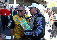 Jul. 21, 2013; Morrison, CO, USA: NHRA funny car driver Jeff Arend (left) talks with John Force as he holds 1000 dollars worth of lottery scratchers during the Mile High Nationals at Bandimere Speedway. Mandatory Credit: Mark J. Rebilas-