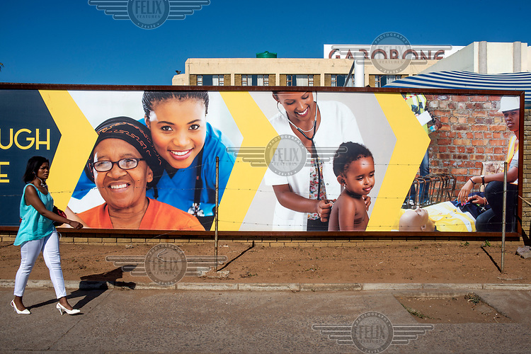 A woman walks past a billboard displaying images related to health at Gaborone hospital.