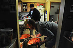 Mike Padgett, 30, and cousin Garrick Leitelt, 38, check on pizzas in the oven in the kitchen of the home they share with extended family in Chicago Ridge, Illinois on April 21, 2015.  Padgett is a student at the University of Illinois Chicago doing an externship in the neuroscience imaging and microscopy lab and bar tends at the Drum and Monkey on campus for extra cash.