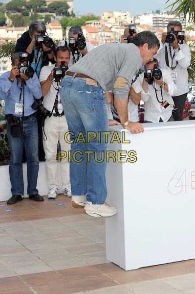 ANTONIO BANDERAS.'The Skin I Live In' photocall (La piel que habito) 64th International Cannes Film Festival, France.19th May 2011.full length grey gray top jeans denim side gesture jump jumping climb funny climbing profile exercise .CAP/PL.©Phil Loftus/Capital Pictures.