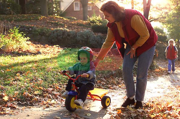 suburban mother pushing toddler son on tricycle along sidewalk, parenting