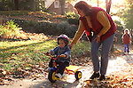 suburban mother pushing toddler son on tricycle along sidewalk, parenting