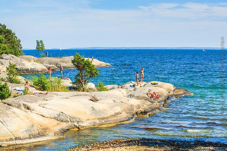 Människor badar vid klippor på Gålö i Stockholms  skärgård.
