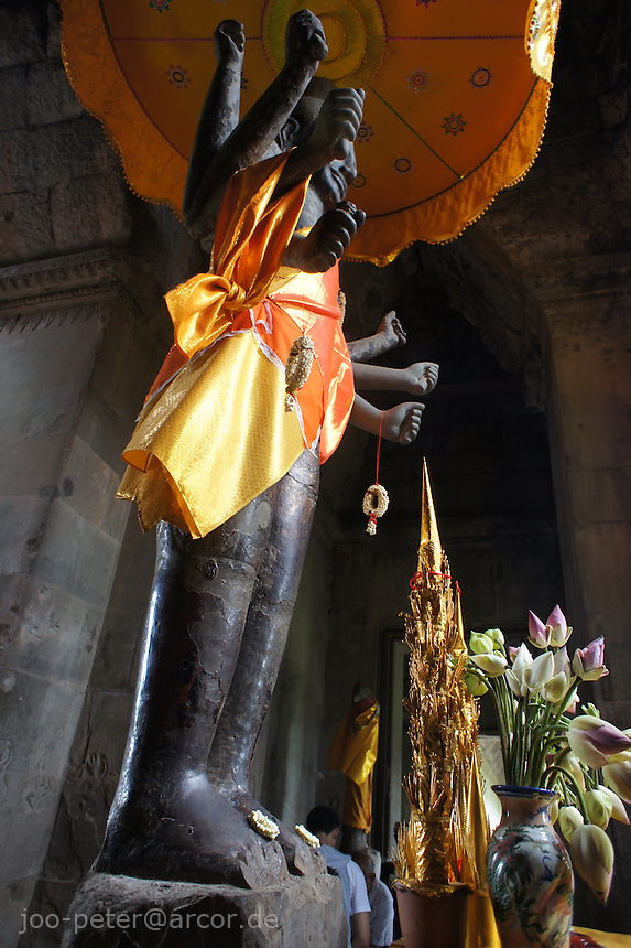 vishnu statue with saffron umbrella, lotus,  entrance of main temple Angkor Wat, right wing side, Cambodia, August 2011. Main temple Angkor what was originally dedicated in 12th century to Lord Vishnu, later became a famous destination of pilgrimage for buddist also