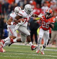 Ohio State Buckeyes running back Carlos Hyde (34) runs by Illinois Fighting Illini defensive back Jaylen Dunlap (28) during the second half of Saturday's NCAA Division I football game at Memorial Stadium in Champaign, Il., on November 16, 2013. Ohio State won the game 60-35. (Barbara J. Perenic/The Columbus Dispatch)