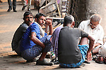 A group of men wearing traditional lunghi wraps gather around a shoe repairer in the streets of Kolkata.