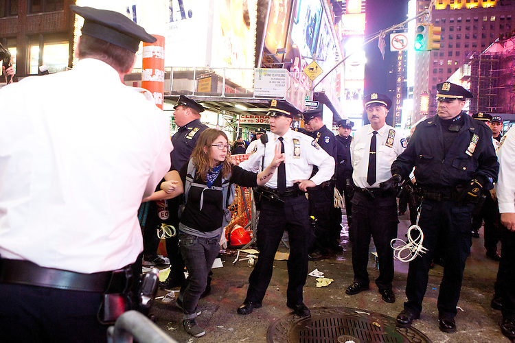 """Protesters with """"Occupy Wall Street"""", having been blocked by barricades for the better part of two hours in Times Square are freed by the suddenly accomodating NYPD who decide to let them cross the street on October 15, 2011 in New York City.  While crowd estimates numbered in the tens of thousands, police tactics (including nets, motor scooters, barricades, arrests, and intimidation by riders on horseback) prevented the crowd, which had been split up, from joining together as one in the middle of Times Square.  By the time the NYPD removed some barricades and let protesters join each other their numbers had dwindled significantly as many went to a rally in Washington Square Park rather than wait in Times Square."""