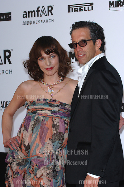 Actress MILLA JOVOVICH with fashion designer & amfAR chairman KENNETH COLE at the amfAR Cinema Against AIDS Gala at the Moulin de Mougins restaurant in the South of France. Tha Gala is one of the main events at the 58th Annual Film Festival de Cannes..May 19, 2005 Cannes, France..© 2005 Paul Smith / Featureflash
