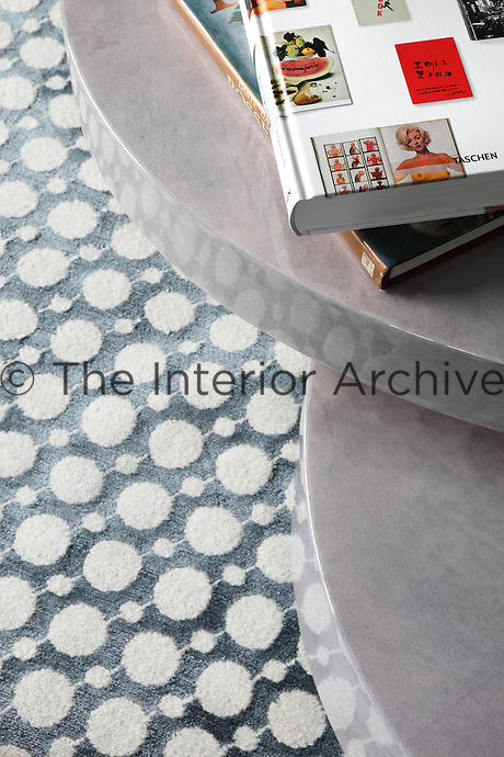 Detail of the circular pattern of the blue-grey and white rug in the living room refelcted in the shining stone slabs of the coffee table