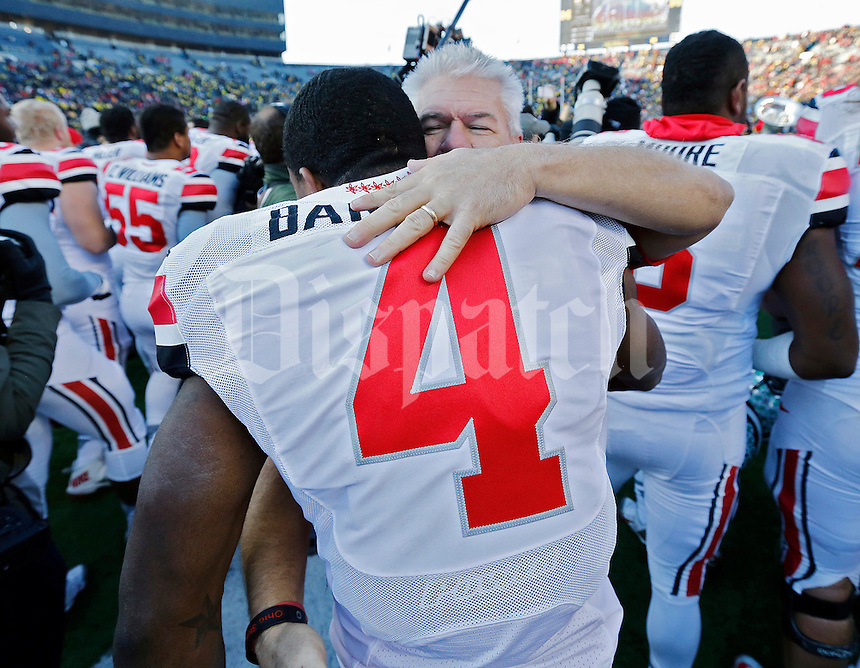 Ohio State Buckeyes safety C.J. Barnett (4) hugs Buckeyes' cornerbacks coach Kerry Coombs after beating Michigan Wolverines 42-41 during their college football game at Michigan Stadium in Ann Arbor, Michigan on November 30, 2013.  (Dispatch photo by Kyle Robertson)