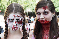 2 woman participants in the zombiewalk prague may 2014. The front woman with plaits and one contact and blood running down her face from her forehead. The other with theater blood on her chin. Both brown hair.